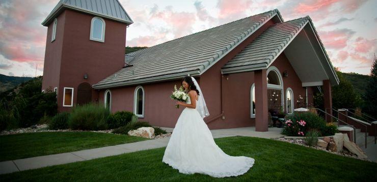 bride with bouquet in fron of wedding chapel in Colorado