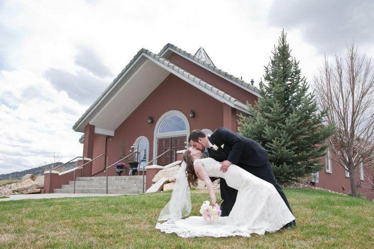 Groom kissing bride in front of wedding chapel in Colorado